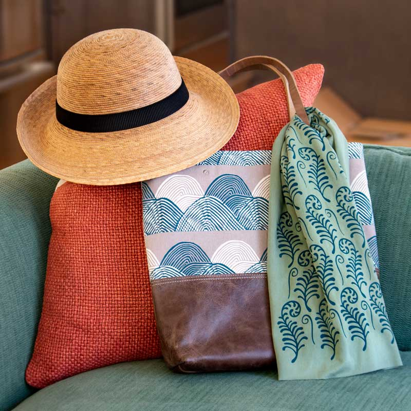 A hat and bag being displayed on a sofa